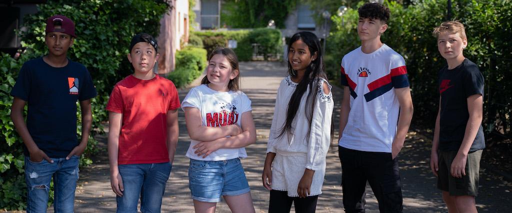 sechs glückliche Kinder, im Alter von 10 bis 12 Jahren, stehen nebeneinander, lachen und blicken in die Ferne